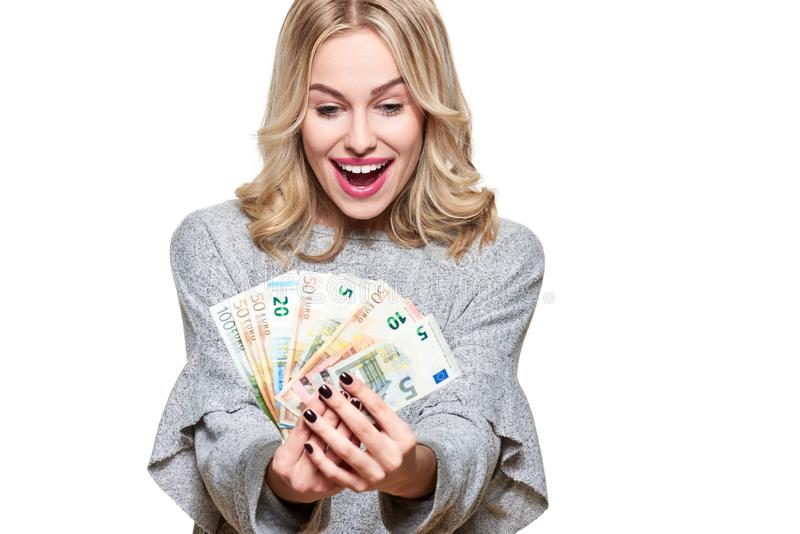 Super excited young woman in grey sweater holding bunch of Euro banknotes, celebrating winning lottery.Woman holding lots of money. Super excited young woman in royalty free stock images