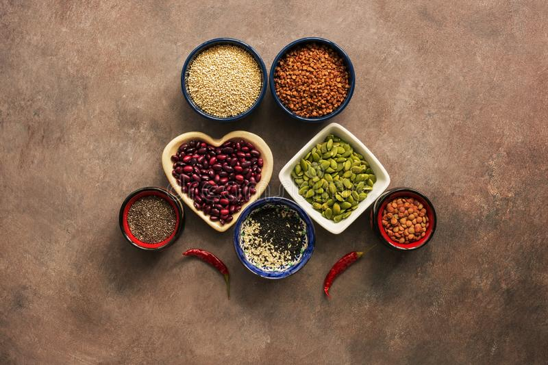 Super food cereals, legumes, seeds and chili peppers on a brown background. Chia, quinoa, beans, buckwheat, lentils, sesame,. Super food cereals, legumes, seeds stock photos