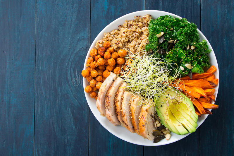 Super foods buddha bowl. Buddha bowl with kale salad, quinoa, roasted chickpeas, grilled chicken breast, avocado, baked sweet potatoes, leek sprouted seeds, pine stock photo