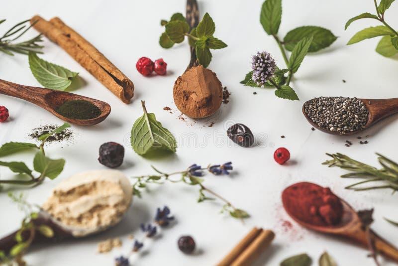 Super foods: maca proszek, beetroot proszek, chia i konopie, spirulina w drewnianych łyżkach na białym tle je?? zdrowo poj?cia zdjęcie stock