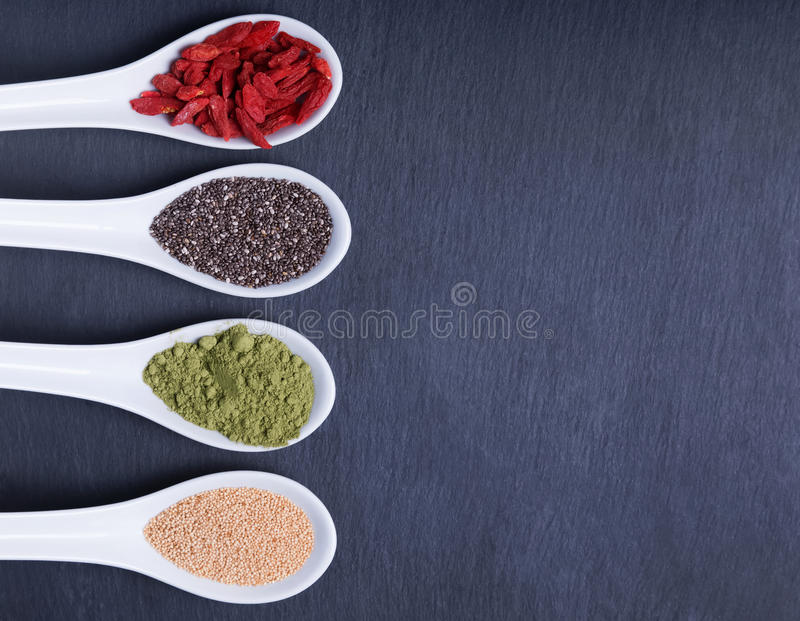 Super foods in the spoons. On the black background, top view stock photography