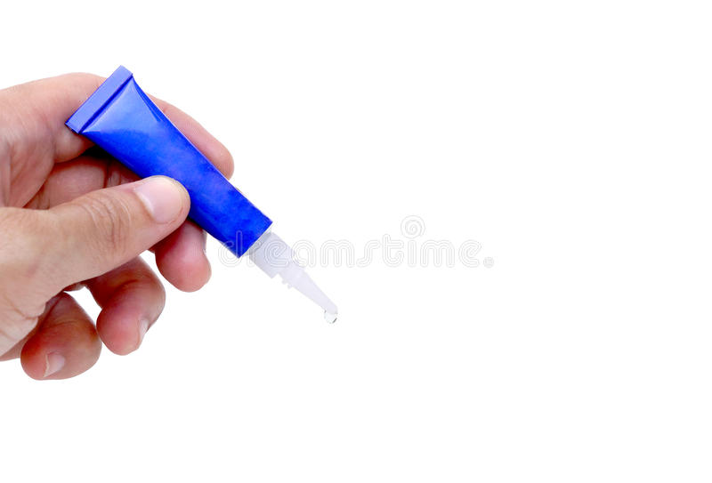 Super glue. Hand holding a superglue tube with a small drop of the glue with blank space to add text royalty free stock photos