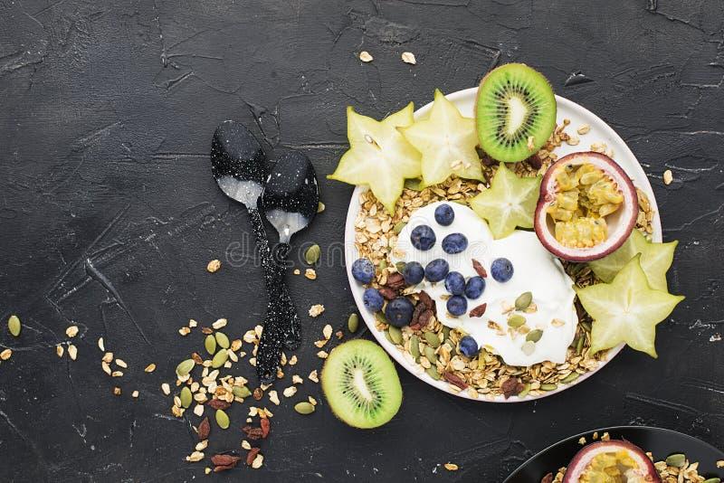 Super goede ontbijtsnack Yoghurt met granola, kiwi, bosbessen, passievrucht, carambola, pompoenzaden, goji royalty-vrije stock afbeeldingen