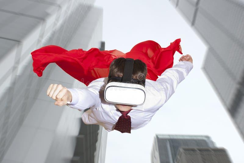 Super héroe del hombre de negocios que lleva los vidrios de la realidad virtual fotografía de archivo