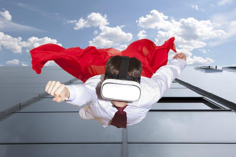 Super héroe del hombre de negocios que lleva los vidrios de la realidad virtual foto de archivo libre de regalías