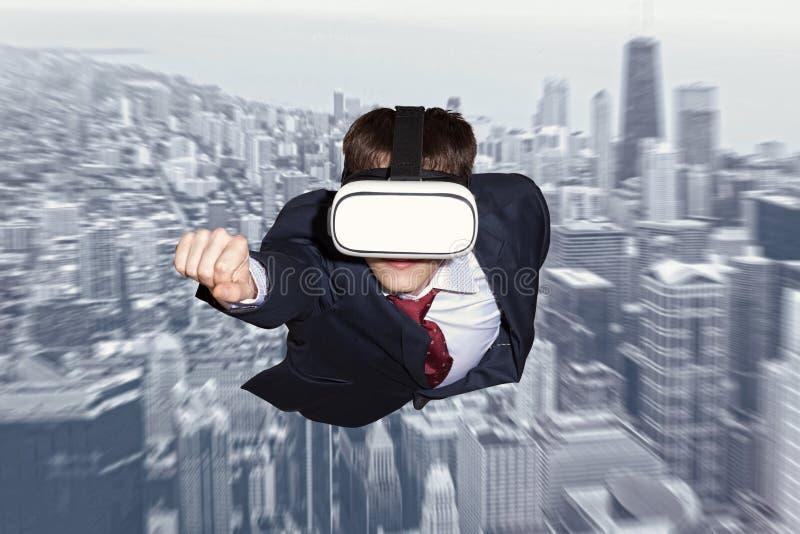 Super héroe del hombre de negocios que lleva los vidrios de la realidad virtual foto de archivo