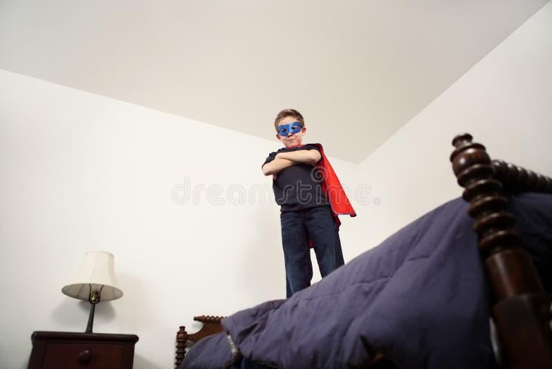 Super héroe del muchacho en cama imágenes de archivo libres de regalías