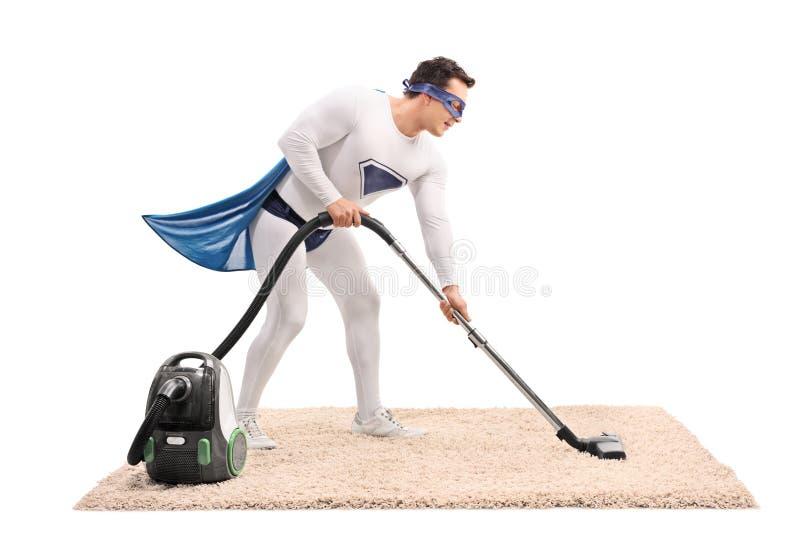 Super héroe joven que limpia una alfombra con la aspiradora foto de archivo