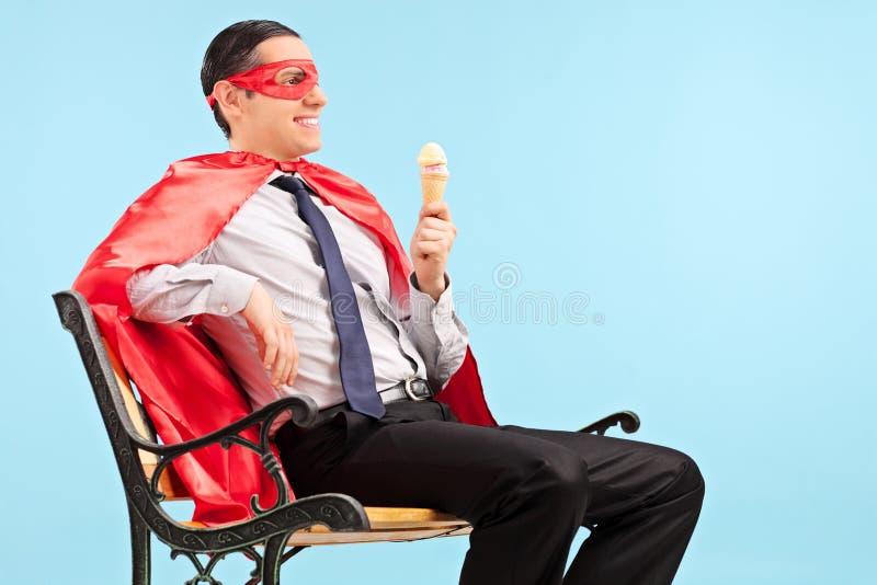 Super héroe que sostiene un helado asentado en banco foto de archivo