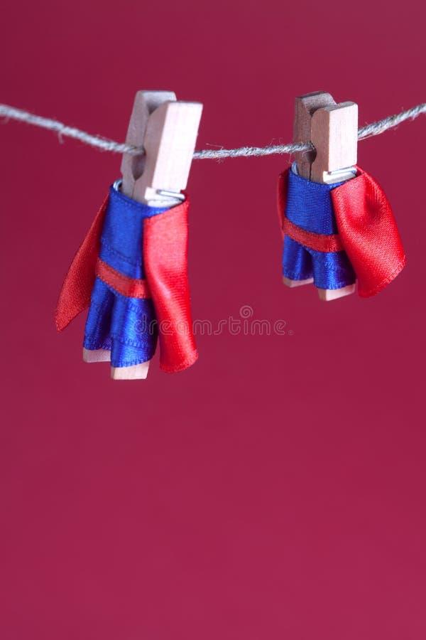 Super héroes de la clavija de la pinza del juguete en cuerda para tender la ropa de la cuerda Pequeño fondo estupendo grande del  foto de archivo
