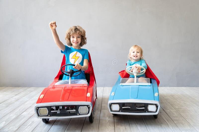 Super héroes de los niños que juegan en casa imágenes de archivo libres de regalías