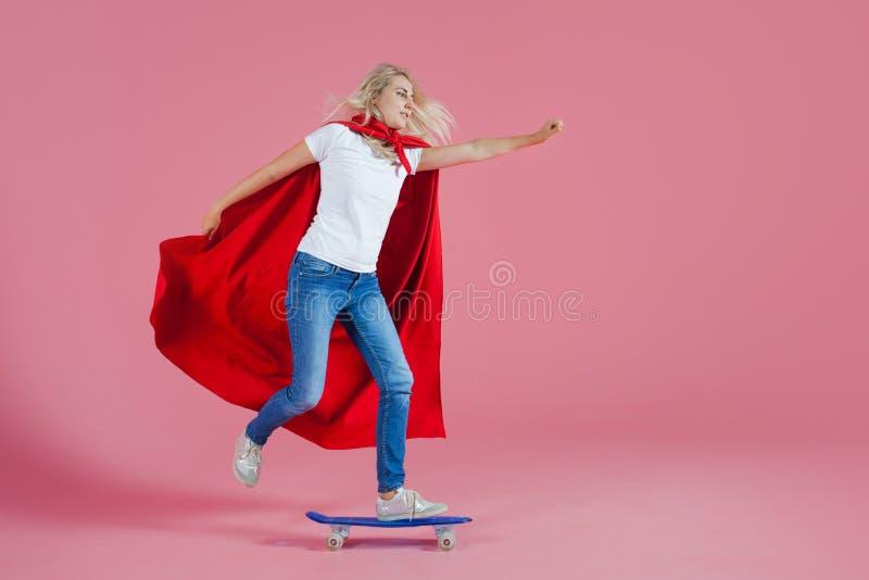 Super héros sur une planche à roulettes Jeune femme drôle dans l'image d'un super héros à la délivrance photo libre de droits