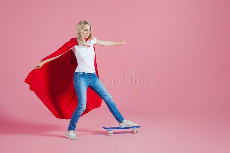 Super héros sur une planche à roulettes La jeune femme drôle dans l'image d'un super héros monte une planche à roulettes photos libres de droits
