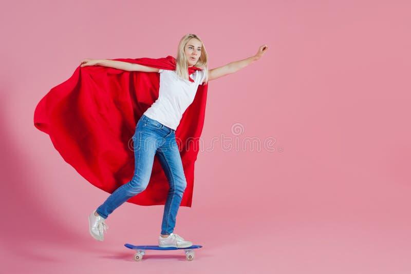 Super héros sur une planche à roulettes La jeune femme drôle dans l'image d'un super héros monte une planche à roulettes images libres de droits