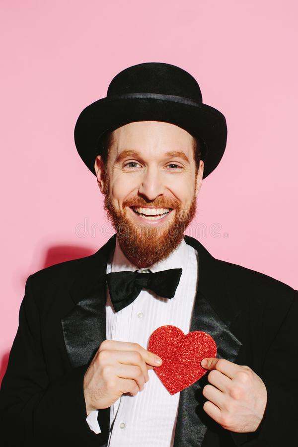 Super happy man smiling with a heart in his hands. Happy man in a tuxedo and top hat holding a red heart. Being very happy and hopeful for the relationship to stock photos