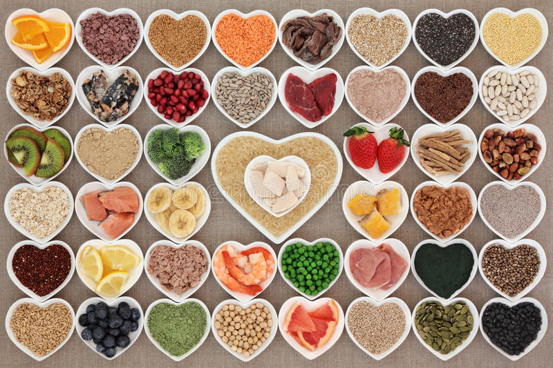 Super Health Food. Large health and body building high protein super food in heart shaped bowls with meat, fish, supplement powders, seeds, cereals, grains royalty free stock photography