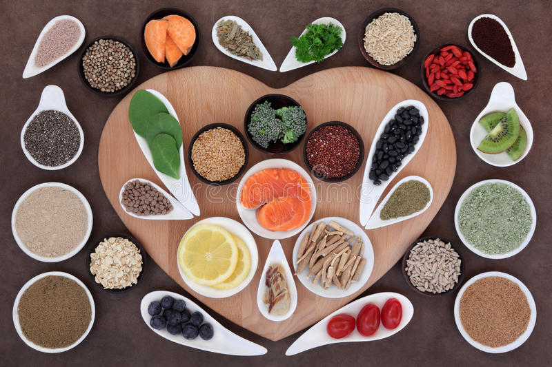 Super Health Food. Selection in bowls on a heart shaped board over lokta paper background stock image