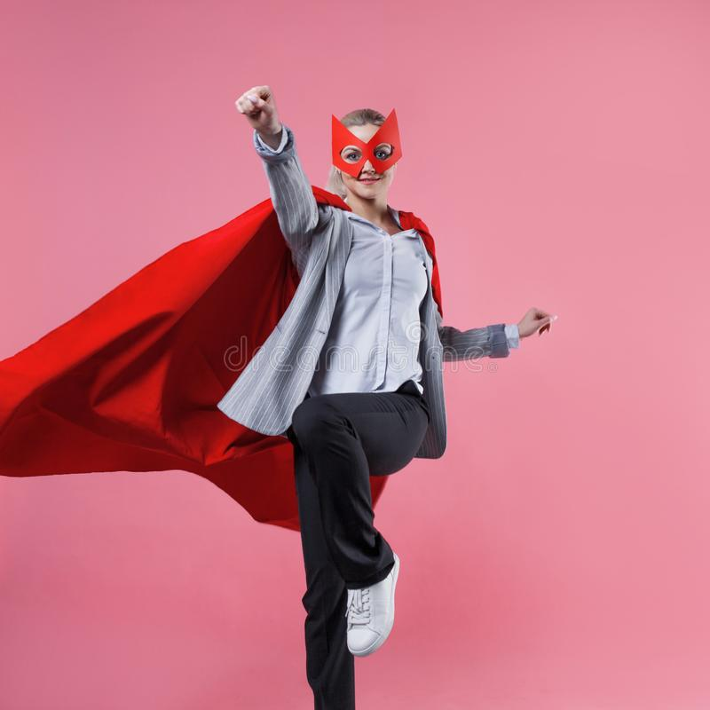Super-herói atrativo novo da mulher Menina em um terno de negócio e uma máscara com o casaco vermelho do herói foto de stock