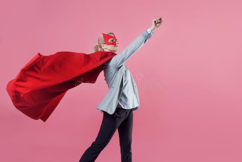 Super-herói atrativo novo da mulher Menina em um terno de negócio e uma máscara com o casaco vermelho do herói fotografia de stock