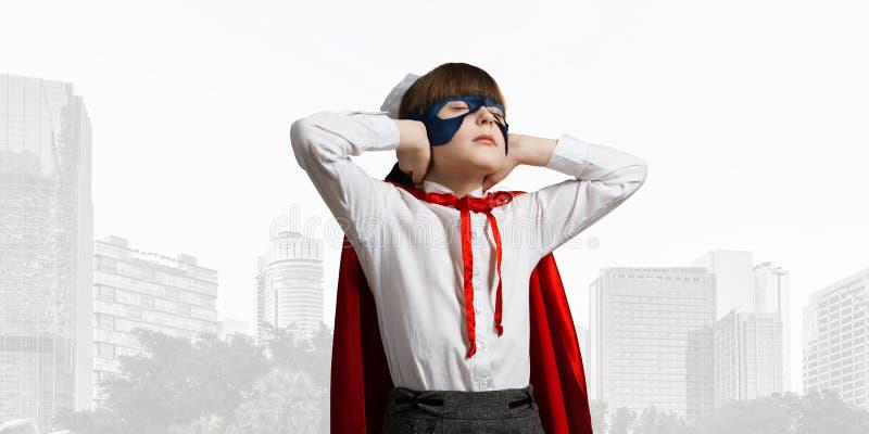 Super-herói da menina da criança contra o fundo da arquitetura da cidade irritado por sons da cidade imagem de stock