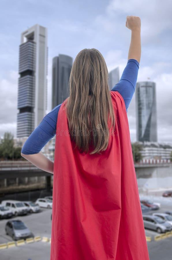 Super-herói da mulher com cabo vermelho e um braço acima fotografia de stock
