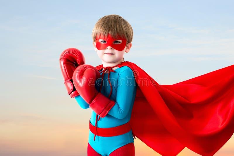 Super-herói do menino no céu do por do sol fotos de stock royalty free
