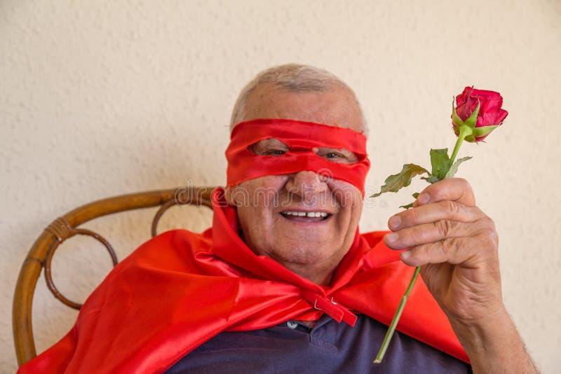 Super-herói idoso que guarda a rosa do vermelho foto de stock royalty free