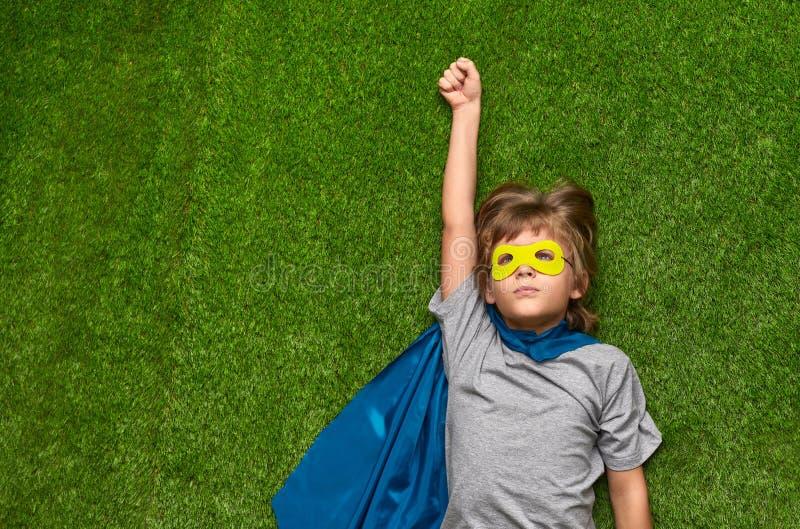 Super-herói pequeno que voa acima sobre o gramado imagem de stock royalty free