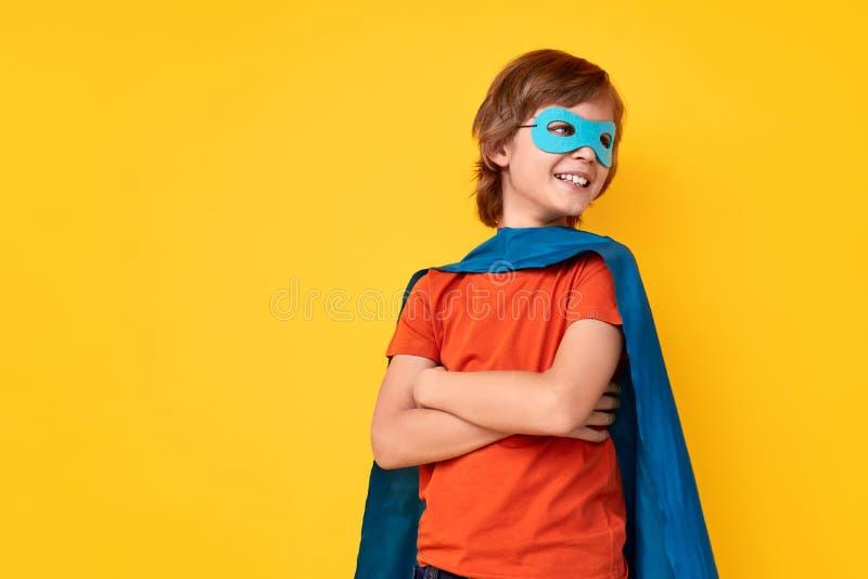 Super-herói pequeno seguro que olha afastado foto de stock
