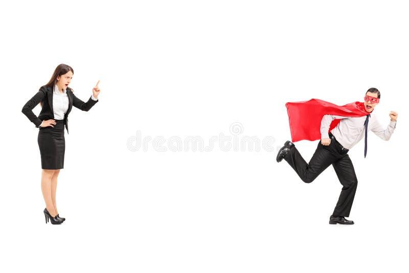 Super-herói que corre longe da mulher de negócios irritada imagens de stock