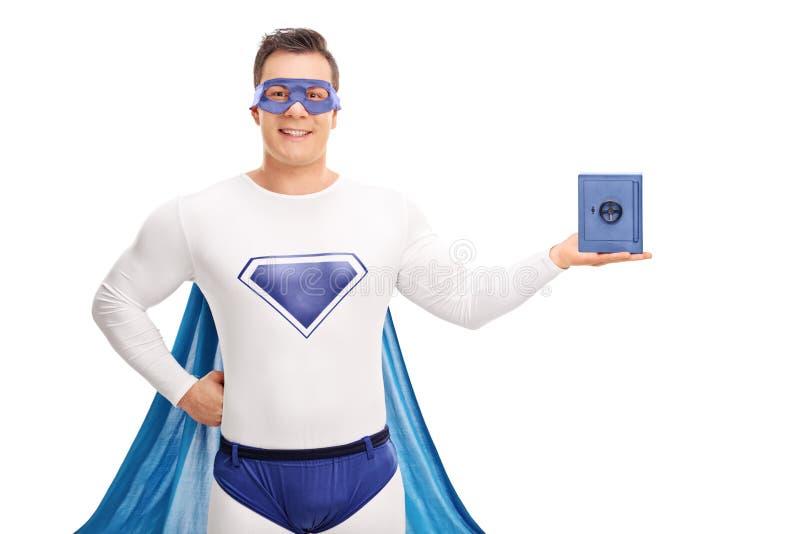 Super-herói que guarda um cofre forte azul pequeno fotos de stock