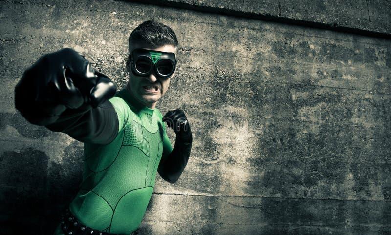Super-herói que perfura seu inimigo imagem de stock royalty free