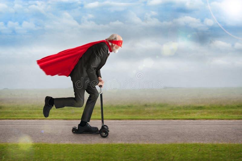 Super-herói superior que monta um 'trotinette' fotos de stock royalty free