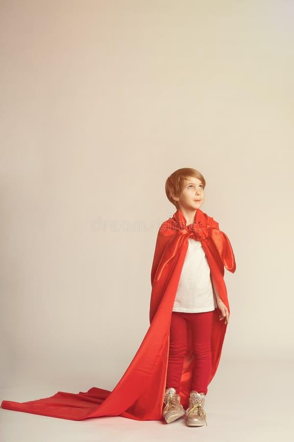 Super hero girl in red cape posing in studio. Child in superwoman costume stock photos