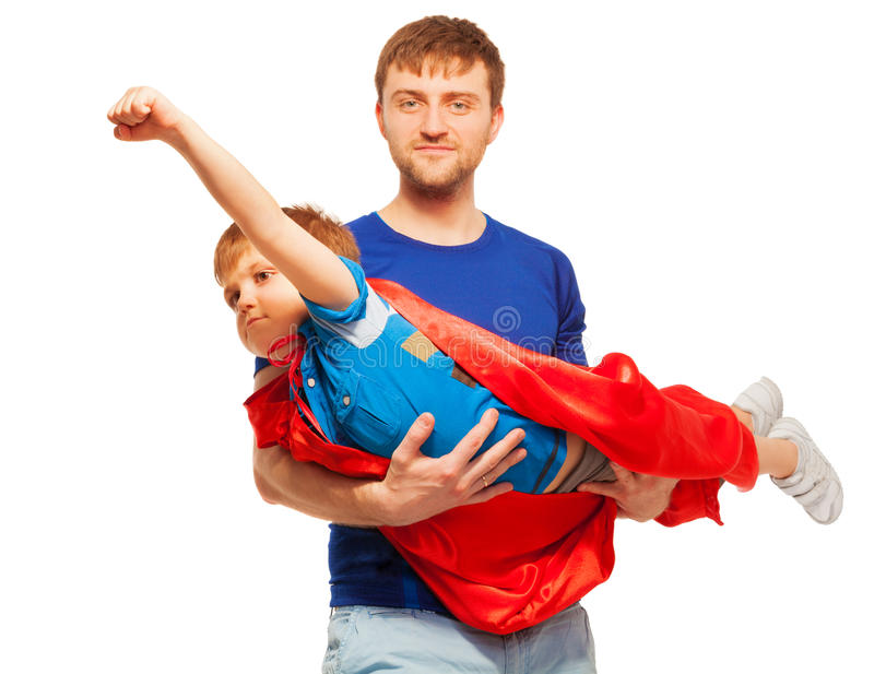 Super hero kid having fun with his dad. Super hero kid, wearing red coat having fun with his dad, isolated on white royalty free stock images