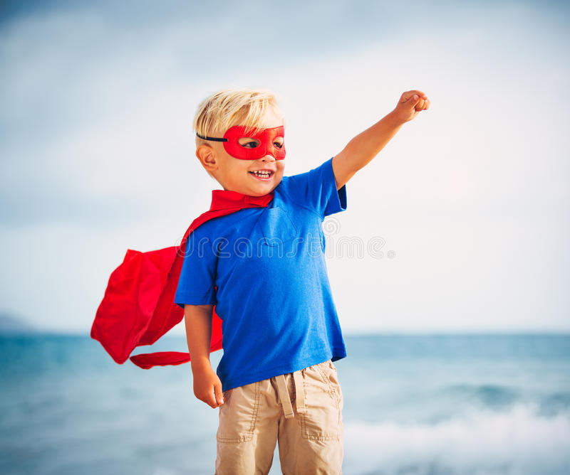 Super Hero kid with a mask flying. Super Hero Kid in red blue dress by the ocean royalty free stock photos