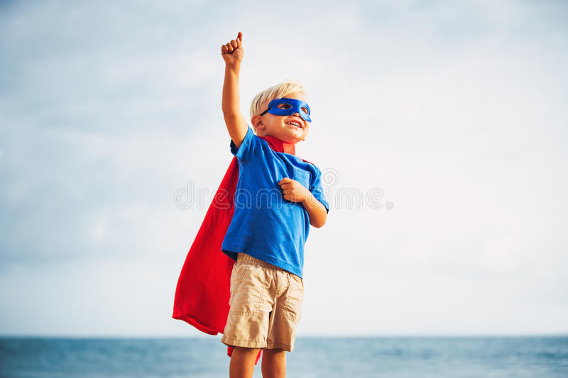 Super Hero kid with a mask flying. Super Hero Kid in red blue dress by the ocean royalty free stock images