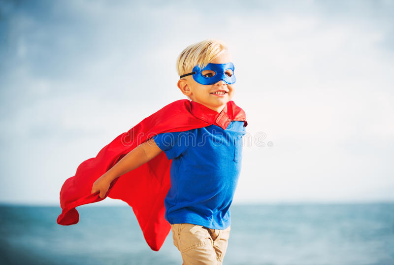 Super Hero kid with a mask flying. Super Hero Kid in red blue dress by the ocean royalty free stock photography
