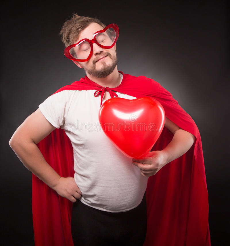 Super hero man in love. Posing with his eys closed while holding red heart in his hand isolated on black background in studio stock images