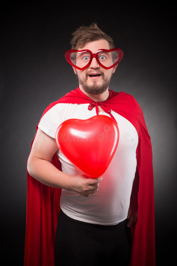 Super hero man in love. Posing with red heart isolated on black background. Handsome man with funny glasses on posing in studio royalty free stock images