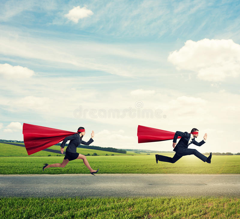 Super heroes in red mask and cloak running. Fast on the road at outdoors royalty free stock photos