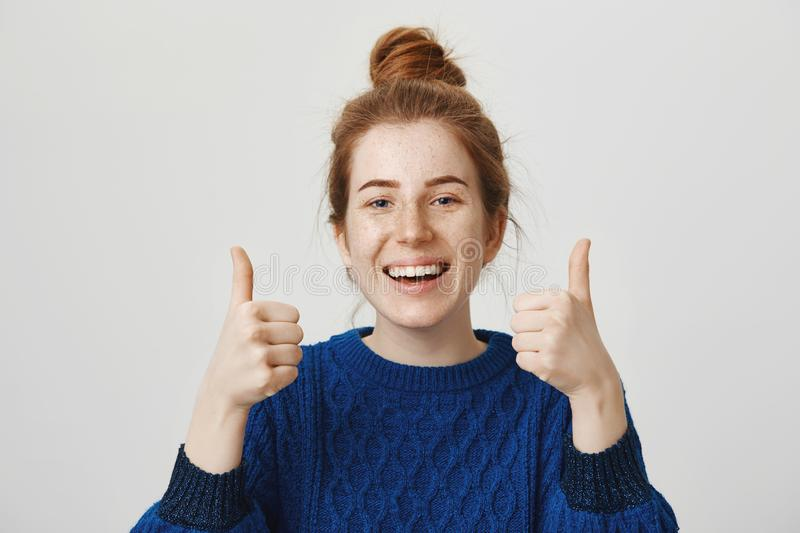 Super, I support your idea. Portrait of beautiful ordinary redhead female student in bun and winter sweater showing royalty free stock images