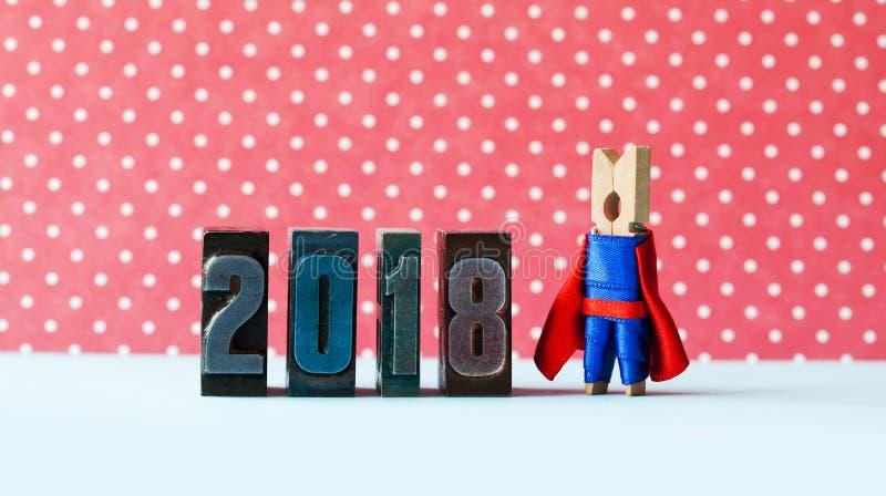 Super inspiration 2018 new year greeting card. Creative superhero leader posing near retro letterpress digits. Metaphor royalty free stock photo