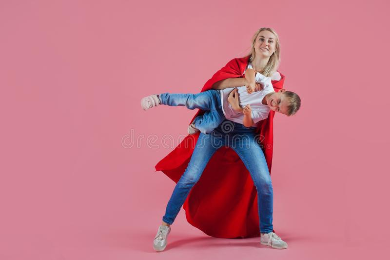 Super Mamma de gelukkige familie, een jonge blonde vrouw in een rode Kaap en haar zoon springen en stijgen op stock foto