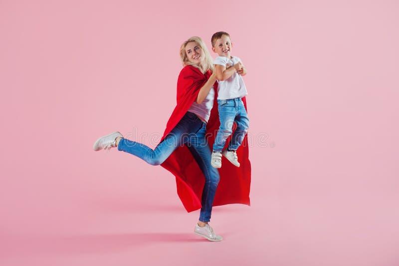 Super Mamma De pretfamilie, een jonge blonde vrouw in een rode Kaap en haar zoon springen en stijgen op royalty-vrije stock foto's