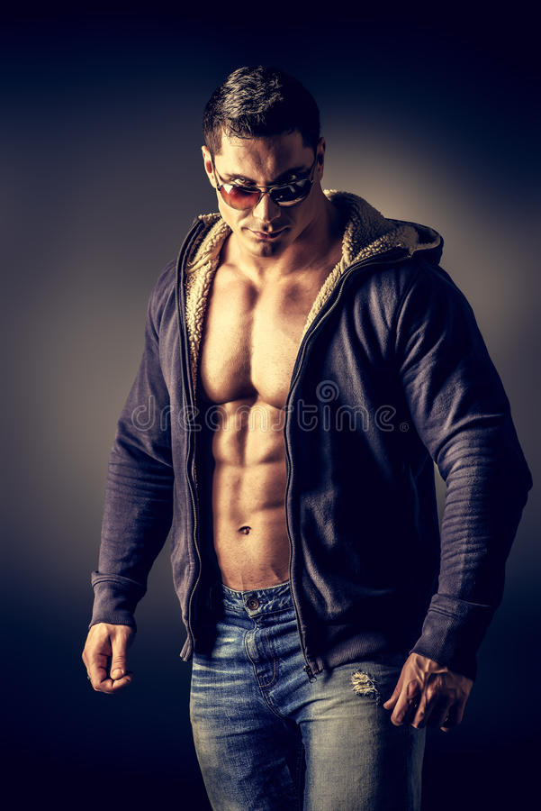 Super man style. Portrait of a muscular young man posing over dark background stock image