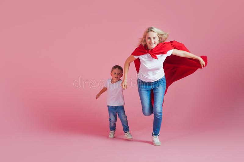 Super mom and her son run forward. Fun family, a young blond woman in a red Cape as superhero stock photo
