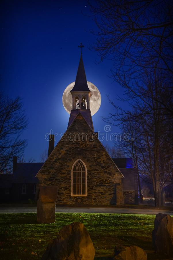 A super moon above the Anglican stone-field church, St. Peter`s of Cookshire-Eaton in Estrie, Quebec, Canada royalty free stock image