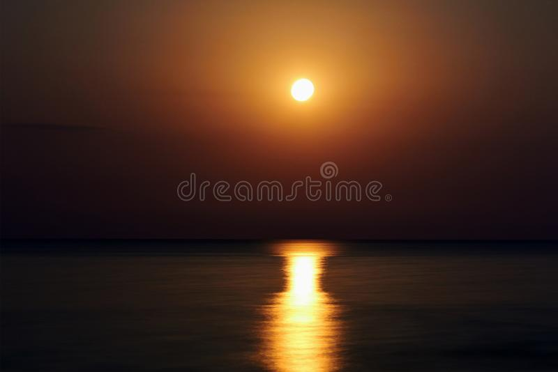 The super moon on the beach. The moon track is reflected in the water. The night moon came up over the water. Full moon on the bea. Ch royalty free stock photography