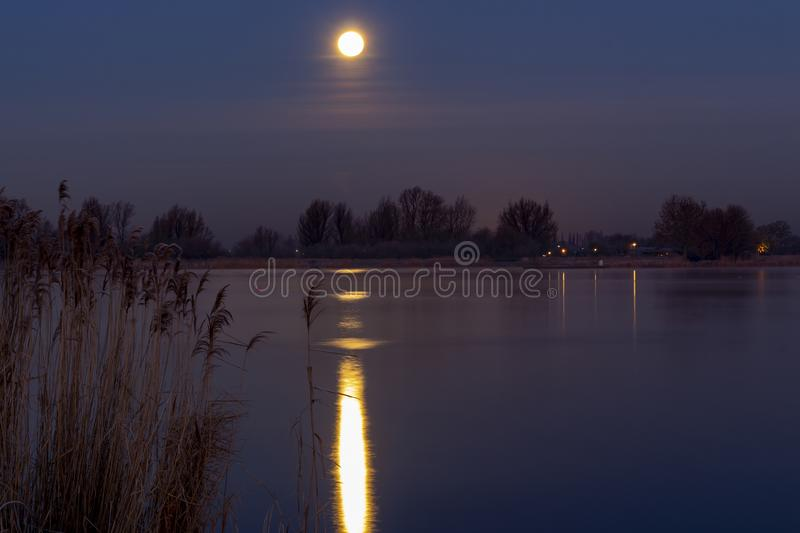 The super Moon is during the cold dawn reflected in the water of the Zoetermeerse plas in Zoetermeer, Netherlands. The super Moon is during the cold dawn stock photo